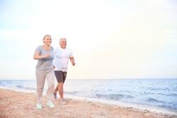 Sporty mature couple running on sea beach