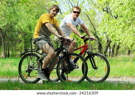 Sporty mature man and a young man cycling in a park.