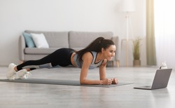 Sporty millennial woman planking in front of laptop, living room interior, side view, copy space. Healthy young lady in sportswear exercising at home, watching online fitness class