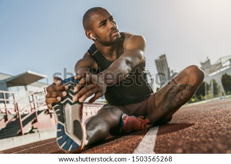 Sporty muscular african male athlete in earphones looking away, stretching legs while sitting at the stadium race track