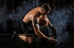 Sporty muscular man working out with barbell at a gym