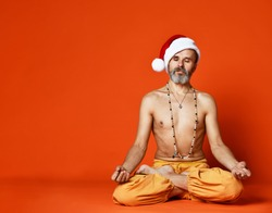 a67fea12 Sporty old man senior in red Santa Claus Christmas hat meditating in  cross-legged yoga