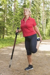 Sporty older woman warming up and stretching legs holding nordic walking poles before exercise at a track outdoors.