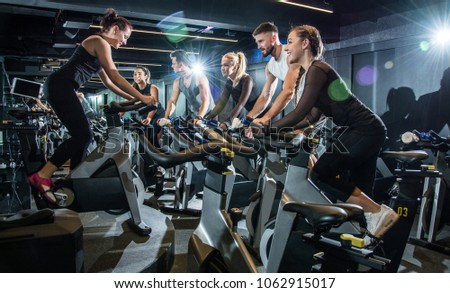 Sporty people on riding exercise bikes with assistance of their trainer during cycling class