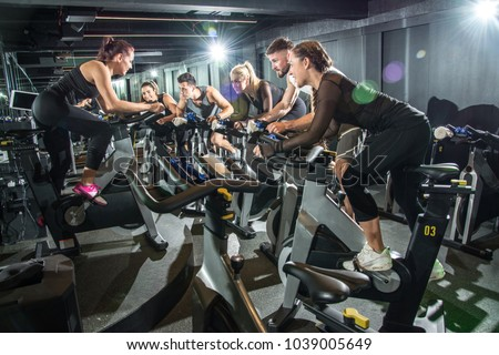 Sporty people riding indoor bicycles on cycling class in the gym.