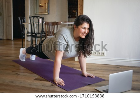 Sporty plus size woman in sportswear working out at home, doing plank on yoga mat in front of open laptop, repeating instructions by professional fitness trainer watching online video tutorial