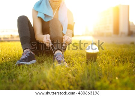 Sporty runner woman tying laces before training. Marathon. Green detox smoothie.  - Shutterstock ID 480663196