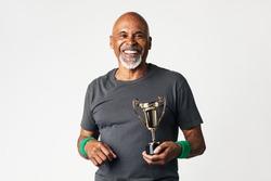 Sporty senior man holding a golden trophy