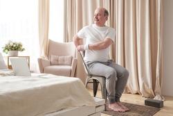 Sporty senior man practicing yoga using chair, doing Parivrtta Utkatasana