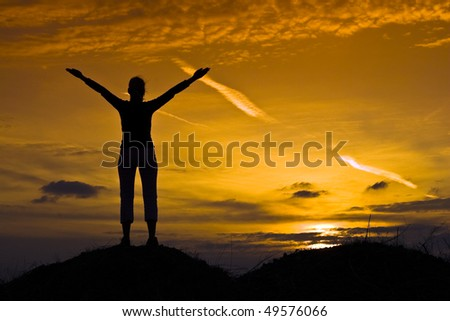 Sporty, slim girl relaxing in the sunset. - stock photo
