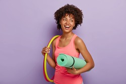 Sporty slim lady with healthy dark skin, Afro hairstyle, exercises with hula hoop, carries rolled up karemat, dressed in pink vest, has toothy smile, poses indoor. Healthy lifestyle, gymnastic concept