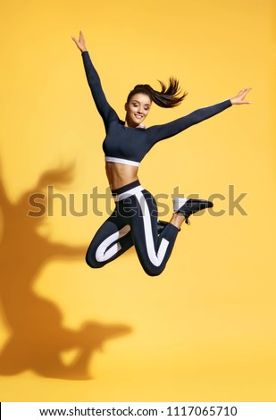 Sporty smiling woman jumping up in silhouette on yellow background. Dynamic movement. Sport and healthy lifestyle #1117065710