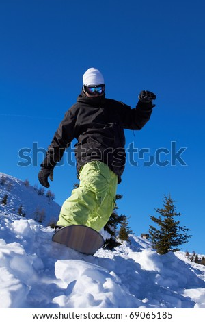 Sporty snowboarder riding on snow in high mountains - stock photo