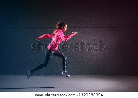 Sporty strong sporty woman running against black wall.