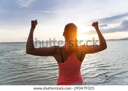 Sporty strong woman raising arms and enjoying freedom and success towards the sun and sea on sunset at the beach. Successful female athlete against the sun.