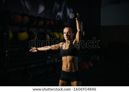 Sporty woman bodybuilder with perfect muscular body in black sportswear is lifting kettlebell overhead during weight training workout. Concept of healthy lifestyle and workouts in a modern dark gym.