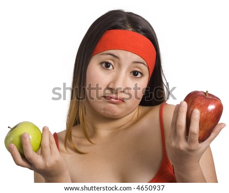sporty woman cannot choose between green and red apple