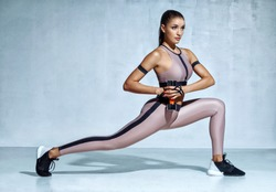 Sporty woman doing lunges with dumbbells. Photo of muscular woman in fashionable sportswear on grey background. Strength and motivation.