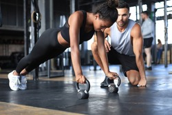 Sporty woman doing push-up in a gym, her boyfriend is watching her.