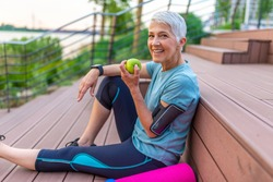 Sporty woman eating apple. Beautiful woman with gray hair in the early sixties relaxing after sport training. Healthy Age. Mature athletic woman eating an apple after sports training