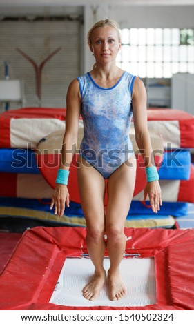 Sporty woman gymnast in bodysuit jumping at  trampoline in sport gym #1540502324
