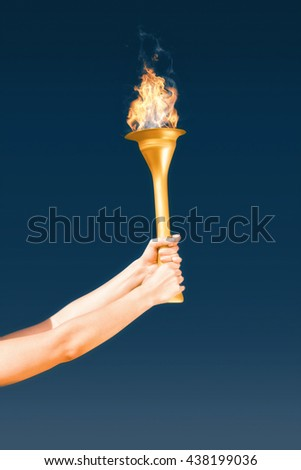 Sporty woman holding Olympic torch against navy sky