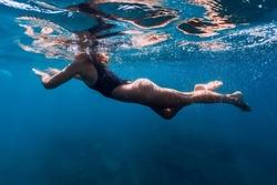 Sporty woman in bikini swimming in blue sea. Activity summer days in ocean