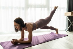Sporty woman in grey sportswear, bra and leggings practicing yoga, doing Push ups or press ups exercise, phalankasana, variation of Plank pose, beautiful girl working out at home or in yoga studio