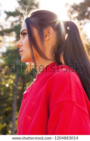 Sporty woman in sporty red clothes. Portrait, close-up in the sunset sunlight