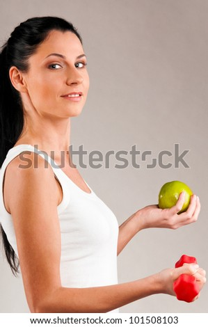 sporty woman is holding red barbell and green apple on grey background