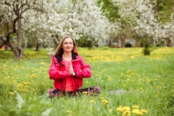 Sporty woman is practicing meditation sitting on the green lawn among blooming trees in spring. Girl is sitting in the lotus position, with her hands in namaste and her eyes closed.