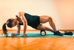 Sporty Woman Massaging Her Legs with Foam Roller
