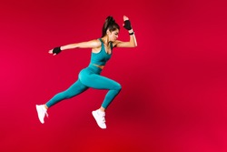 Sporty woman runner in silhouette on red background. Photo of attractive woman in fashionable sportswear. Dynamic movement. Side view. Sport and healthy lifestyle