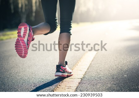 sporty woman running on road at ...