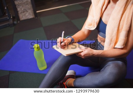 Sporty woman sits on a training mat and writes down future training plans for achieving great results in gym