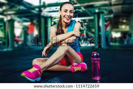 Sporty woman smiling on camera with water after workout in gym