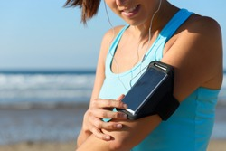 Sporty woman touching phone screen in arm sport band before running on beach. Female athlete listening music while doing sport.