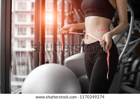 Sporty woman using waist tape line in fitness gym sport club training center near window with condominium background. Lifestyle of people workout exercise sport activity. Diet and weight loss theme. #1170249274