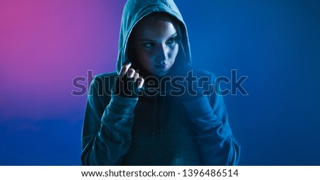 Sporty woman wearing a hooded shirt looking away. Fitness female against colored background with gel effect.