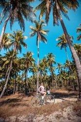 Sporty woman with bicycle in tropical forest, Myanmar, Ngapai