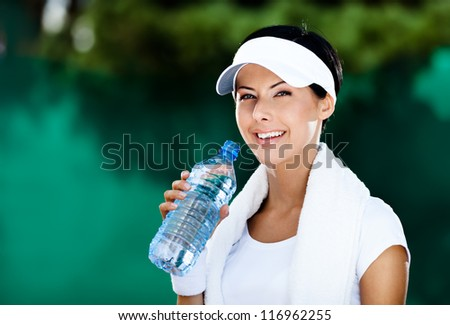 Sporty woman with bottle of water after tennis contest