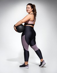 Sporty woman with medicine ball. Photo of model with curvy figure in fashionable sportswear on grey background. Sports motivation and healthy lifestyle