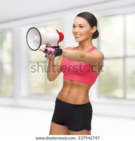 sporty woman with megaphone pointing her finger at something
