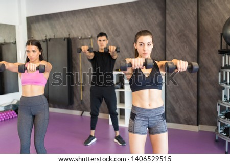 Sporty women and man exercising with dumbbells at health club