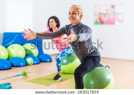 Sporty women doing stretching exercises with fitness stability ball in a sports club.