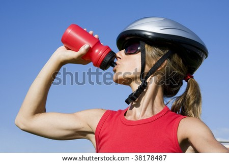 Sporty women with a cycle helmet drinking water
