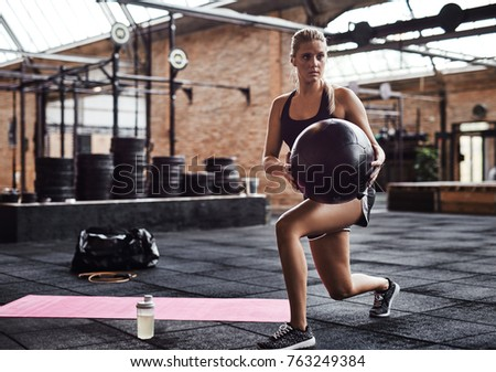 Stock Photo Sporty young blonde woman in gym clothing doing core exercises with an exercise ball while working out alone in a health club