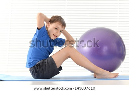 sporty young boy in blue doing exercises
