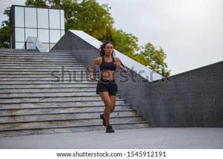 Sporty young female in sporty black clothes and sneakers running down city stairs, looking concentrated in front of herself. Woman fitness jogging workout wellness concept