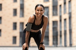 Sporty Young Female Leaning On Knees, Catching Breath After Training Outdoors, Athletic Woman In Stylish Sportswear Relaxing After Stamina Workout, Standing On Urban Street And Smiling At Camera
